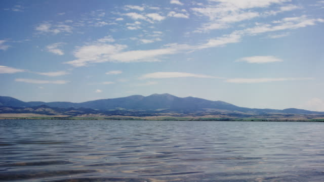 vídeos de stock e filmes b-roll de gentle waves on lake de smet in wyoming with the rocky mountains in the background on a sunny day - margem do lago