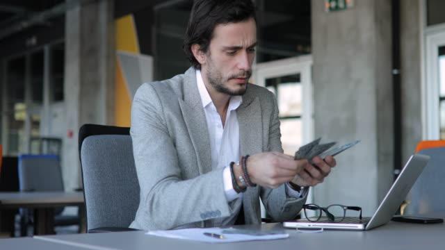 Gentleman counting money in office