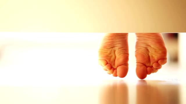Enfant en douceur les pieds sur le sol stratifié UNDERbed inhabituel vue: - Vidéo