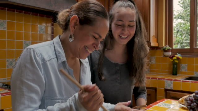 Genuine moment between a mother and daughter laughing and cooking Genuine moment between a hispanic mother and mixed ethnic daughter laughing and cooking together - push in gimbal shot one parent stock videos & royalty-free footage