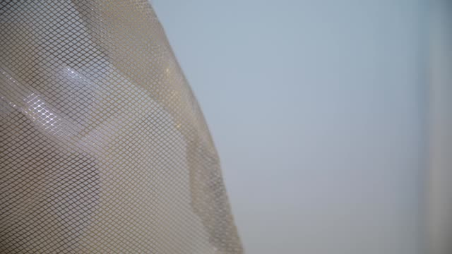 A geometric abstract metal mesh is floating and rotating itself