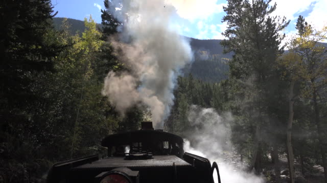 Georgetown Loop Railroad steam engine locomotive train Colorado smoke stack Rocky Mountains Puffing out black smoke, a steam locomotive pulls train cars over the steep grade on the Georgetown Loop Railroad in the Colorado Rocky Mountains. wild west stock videos & royalty-free footage