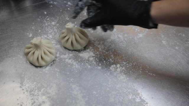 Georgian cuisine workshop male chef cooking khinkali in restaurant.  Closeup shot of chef hands putting Dumplings on tray