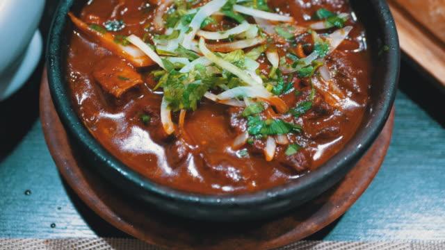 georgiska kötträtt på ketsi i restaurang. chashushuli. hett kött i lerpanna på bordet - marinad bildbanksvideor och videomaterial från bakom kulisserna