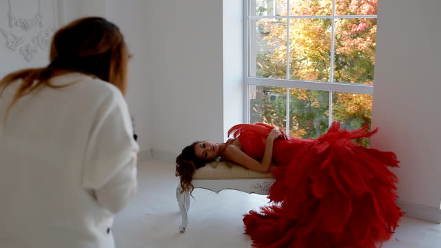 vidéos et rushes de gergeous femme en robe rouge qui pose en studio - prise avec un appareil mobile