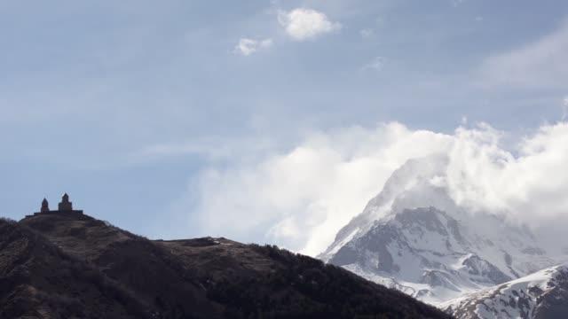 Gergeti Trinity Church and Mount Kazbek shrouded floating clouds. Georgia, Caucasus.