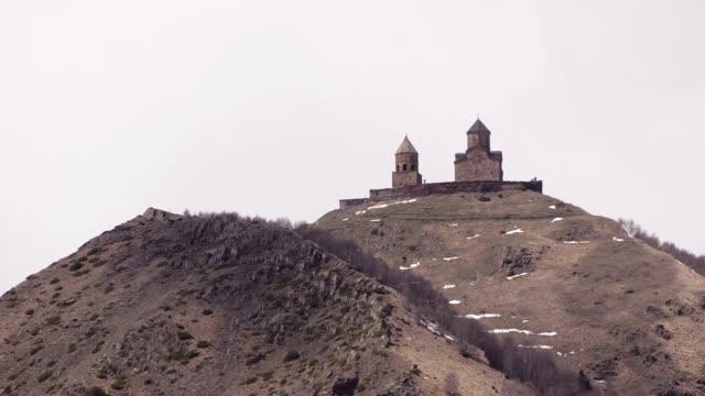 Gergeti Trinity Church in mountains against a white sky. Georgia, Caucasus.