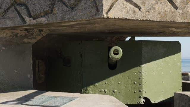 WW2 German canon hidden in bunker on beaches in northern France Normandy WW2 German canon hidden in bunker on beaches in northern France Normandy 4K 3840X2160 30fps UltraHD footage - World War 2 canon inside German bunker French beach  4K 2160p UHD video normandy stock videos & royalty-free footage