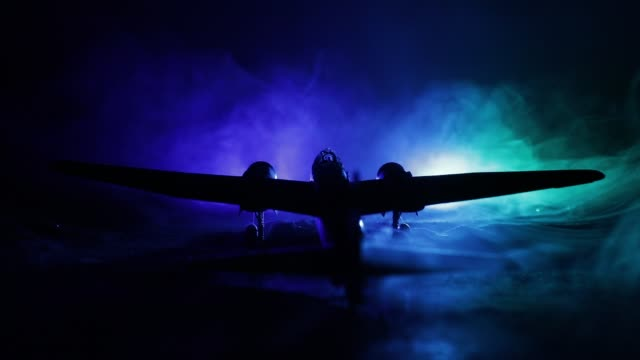 German Junker (Ju-88) night bomber at night. Artwork decoration with scale model of jet-propelled plane in possession. Toned foggy background with light. War scene. Selective focus