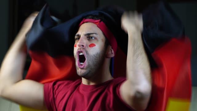 vídeos de stock e filmes b-roll de german young black man celebrating with germany flag - soccer supporter portrait