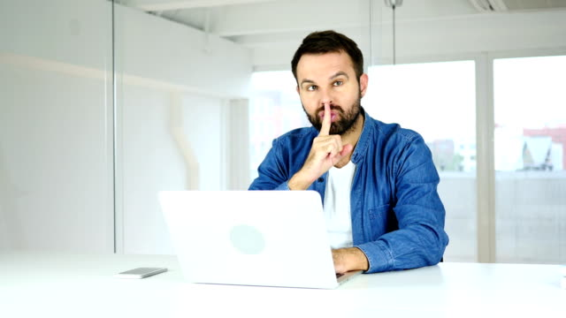 Gesturing of Silence by Man Sitting in Office video