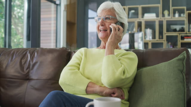 Get connected, get closer to your world 4k video footage of a senior woman using a smartphone at home dial stock videos & royalty-free footage