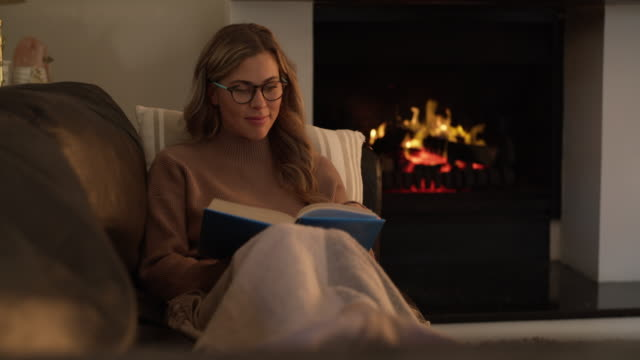 Get out the blankets and books, winter is here 4k video footage of a young woman reading a book while relaxing at home blanket stock videos & royalty-free footage