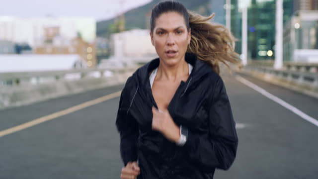 vídeos de stock e filmes b-roll de get running for a healthier you - young woman running city