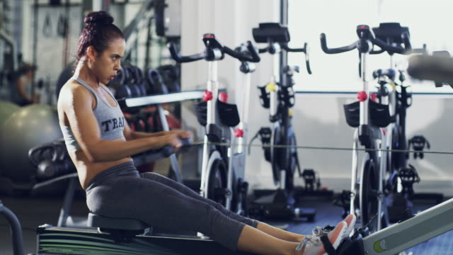 Getting firm through the burn 4K footage of a woman working out on a rowing machine at the gym health club stock videos & royalty-free footage