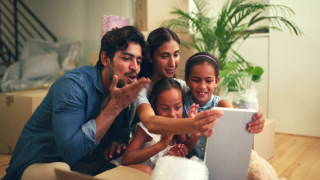 Getting in touch with loved ones has become so easy 4k video footage of a young family on a video call using a tablet in their new home indian family stock videos & royalty-free footage