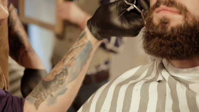 Getting perfect shape. Close-up side view of young bearded man getting beard haircut by hairdresser at barbershop video