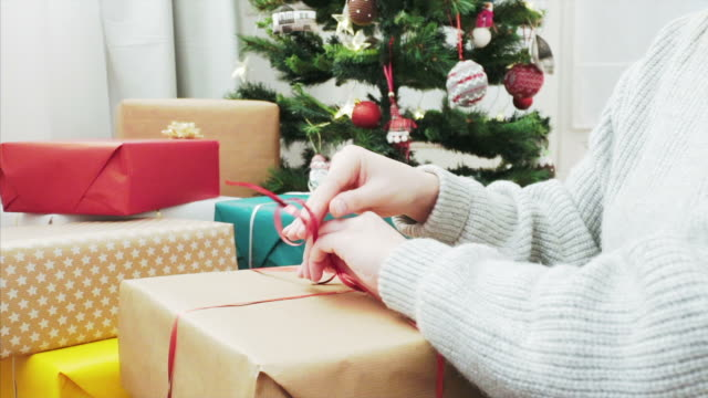 Getting ready for Christmas season! Woman tying ribbon on Christmas gift. She has great Christmas gifts for her family. wrapped stock videos & royalty-free footage