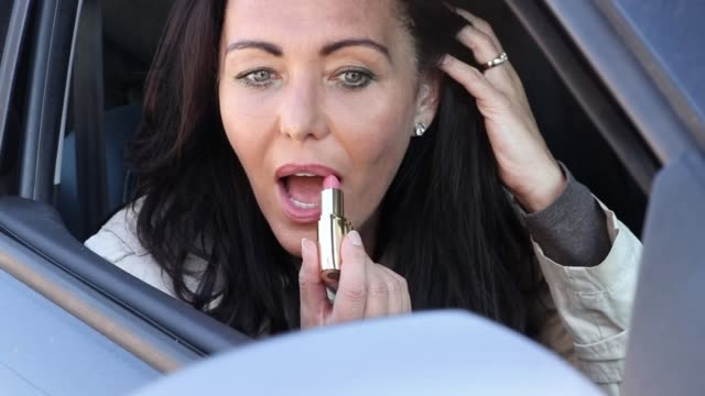 Getting ready, woman applying lipstick in car mirror Front view close up of mature woman putting lipstick on, looking in a car mirror. donna stock videos & royalty-free footage