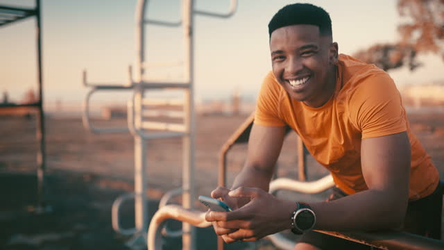 Getting social during his break 4k video footage of a sporty young man using a cellphone while exercising outdoors contented emotion stock videos & royalty-free footage