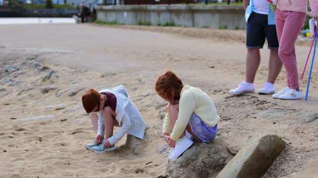 togliersi la sabbia dalle dita dei piedi - capelli rossi video stock e b–roll