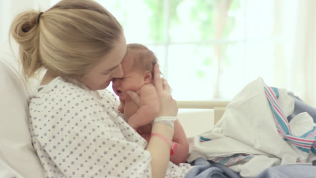 Getting to Know Baby A young mother holds her newborn just after giving birth. She kisses the baby's forehead and holds the infant close. newborn stock videos & royalty-free footage