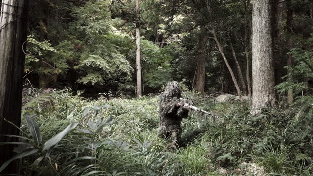 Ghillie suit sniper in the jungle standing up with rifle A soldier in a Ghillie suit camouflaged in the jungle nearly invisible stands up to look around with sniper rifle. camouflage clothing stock videos & royalty-free footage