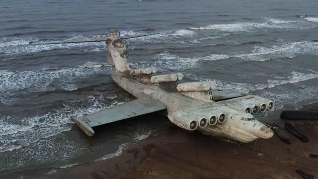 un gigantesco aereo abbandonato si schiantò sulla costa. l'anfibio ibrido si è schiantato sull'aereo. - anfibio video stock e b–roll