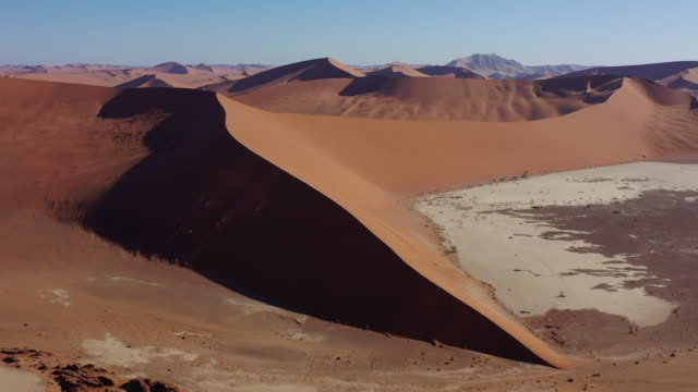 Giant Desert Sand Dune Namibia Sossusvlei Namib-Naukluft Drone 4K Video Giant Dead Vlei Namb Desert Sand Dune. Aerial Drone Video 4K Round Flight in the warm dusk light along giant majestic Desert Sand Dunes in the Namib-Naukluft National Park. Sesriem, Namib-Naukluft National Park, Namibia, South West Africa. swakopmund stock videos & royalty-free footage
