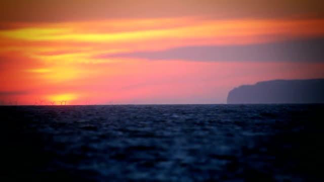 Giant Sunrise Behind Wind Farm At Sea