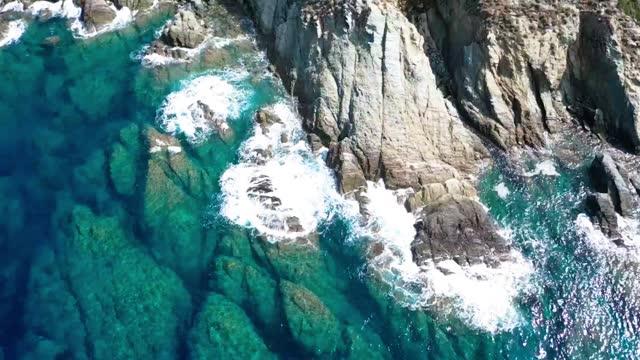 onde giganti che si infrangono sulle scogliere rocciose con schizzo di schiuma bianca. - masso video stock e b–roll