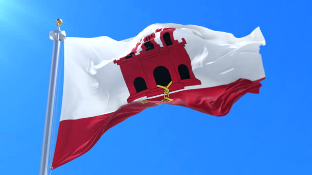 Gibraltarian flag waving at wind with blue sky, loop video