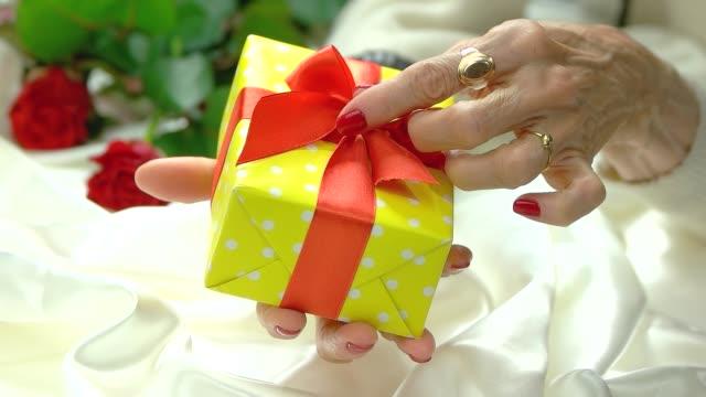 gift box and manicured hand, slow motion. - nastro per capelli video stock e b–roll