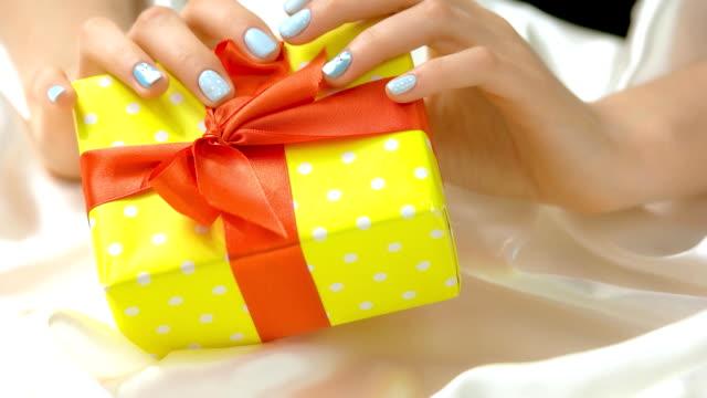 gift box in female manicured hands. - nastro per capelli video stock e b–roll