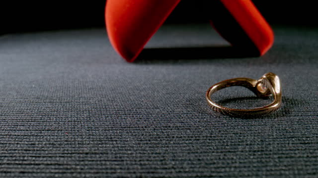 MACRO: Gift box with a golden ring fall on a surface - Slow motion