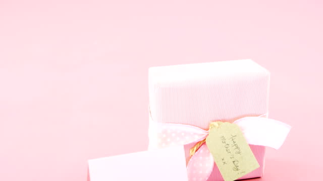 Gift box with happy mother day tag and blank card against pink background video