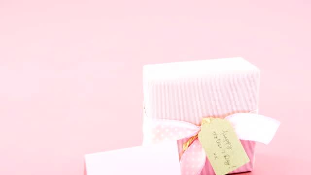 vidéos et rushes de boîte de cadeau avec la balise de jour de mère heureuse et carte vierge sur fond rose - fête des mères