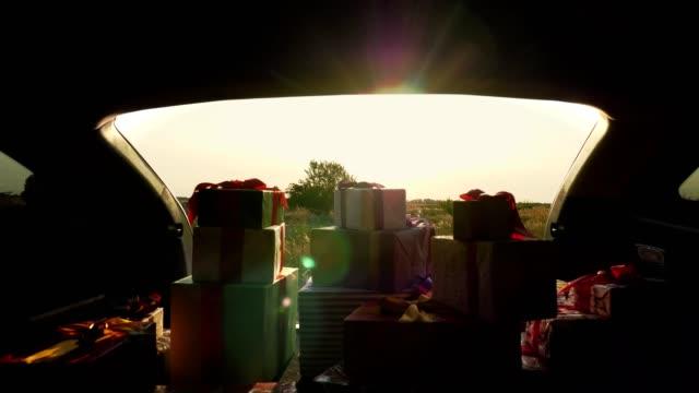 geschenk-boxen im auto. viele schön verpackte boxen, liegen im kofferraum. blick aus dem inneren des autos - nikolaus stiefel stock-videos und b-roll-filmmaterial