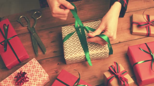 Video gift wrapping. woman tie a green ribbon bow