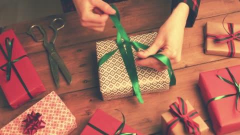 vidéos et rushes de emballage de cadeaux. femme un nœud de ruban vert - cadeau