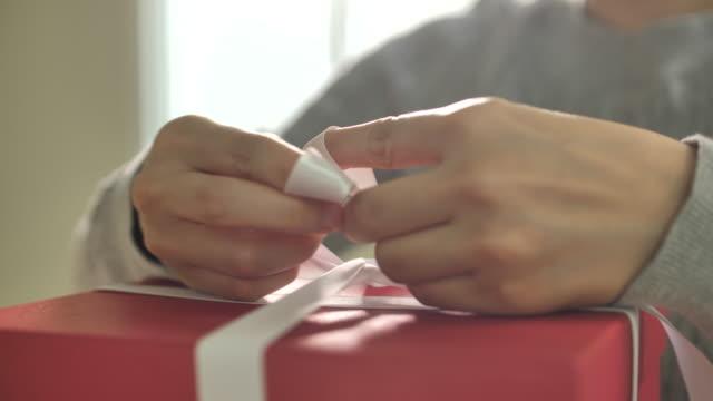 presentförpackning. kvinna slips ett vitt band båge - christmas present bildbanksvideor och videomaterial från bakom kulisserna