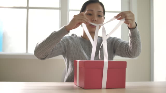 Gift wrapping. woman tie a White ribbon bow