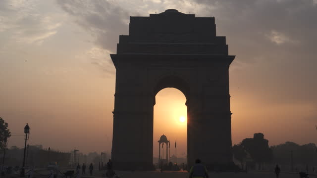 gimbal clip walking towards india gate at sunrise with sun inside arch - nowe delhi filmów i materiałów b-roll