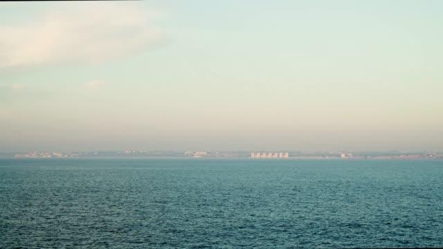 gimbal-aufnahme von meerblick mit gebäuden am horizont in cadiz, spanien - horizont stock-videos und b-roll-filmmaterial