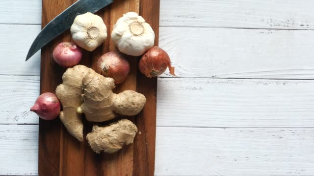 ginger, garlic and onion on chopping board - alliacee video stock e b–roll