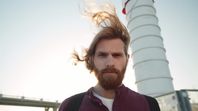 Ginger Man near Lighthouse Low angle view of young stylish man with long red hair and beard standing in front of lighthouse and looking at camera long hair stock videos & royalty-free footage