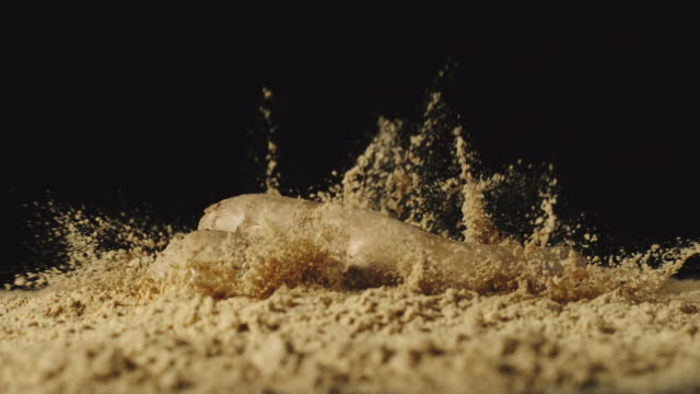 SLOW MOTION: Ginger root falls in powder and powder scatters around SLOW MOTION: Ginger root falls in powder and powder scatters around ginger spice stock videos & royalty-free footage