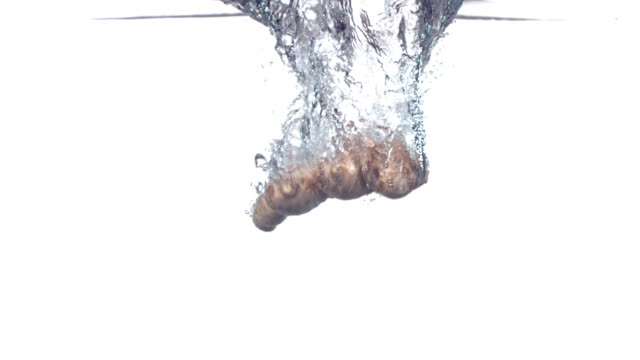 Ginger root splashing into water, slow motion  ginger spice stock videos & royalty-free footage