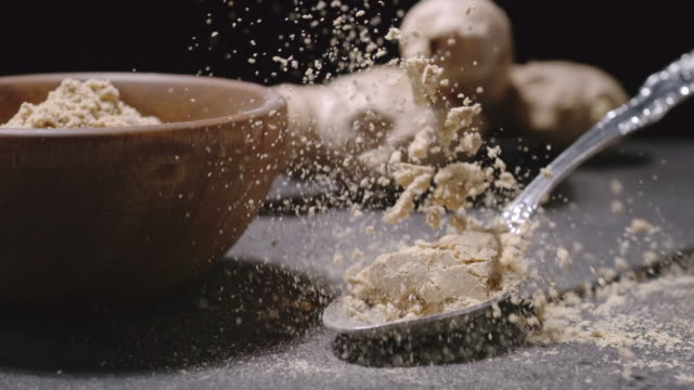 Ginger spice. Spoon with seasoning powder falls down with a splash. SLOW MOTION video