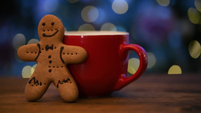 Gingerbread cookie Gingerbread cookie and red cup on Christmas background gingerbread man stock videos & royalty-free footage